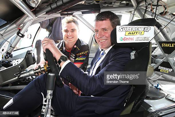 Premier Mike Baird poses with Tim Slade aboard his Supercheap Auto Racing Holden VF Commodore during a V8 Supercars media announcement about the...