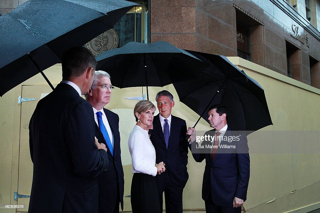 NSW Premier Mike Baird, UK Secretary of State for Defence, Michael Fallon, Australian Minister for Foreign Affairs, Julie Bishop, UK Secretary of State for Foreign and Commonwealth Affairs, Philip Hammond and Australian Minister for Defence, Kevin Andrews gather at the site of the Lindt Cafe Siege at Martin Place on February 2, 2015 in Sydney, Australia. On December 15 2014, gunman Man Haron Monis was shot dead by police after taking hostages at the Lindt Chocolat Cafe in Martin Place. Two other people died, 33-year-old cafe manager Tori Johnson and 38-year-old Sydney barrister Katrina Dawson.
