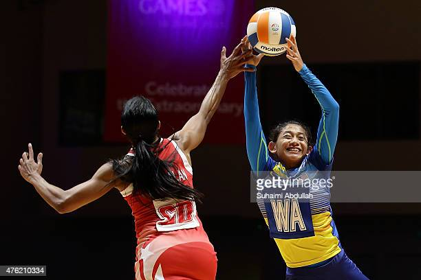 Premila Hirubalan of Singapore and Nurfariha Abdul Razak of Malaysia challenge for the ball during the women's netball gold medal match between...