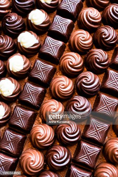 premium collection of dark, milk and white chocolate sweets, selective focus. chocolate background. macro food photography. collection of candies. - chocolate pieces stock photos and pictures
