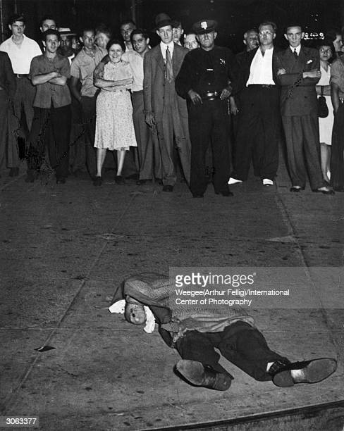 An auto accident victim lies on the New York sidewalk covered with a blanket while a curious crowd of onlookers gathers nearby Photo by...