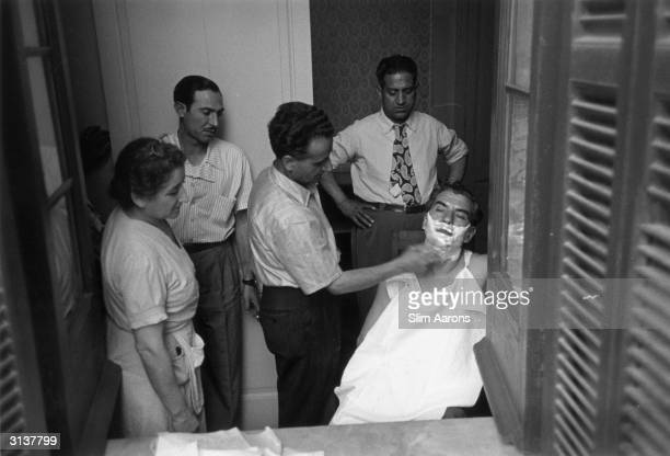 Sicilian born American gangster Charles 'Lucky' Luciano being watched by his entourage as he is given a shave while living in exile in Sicily