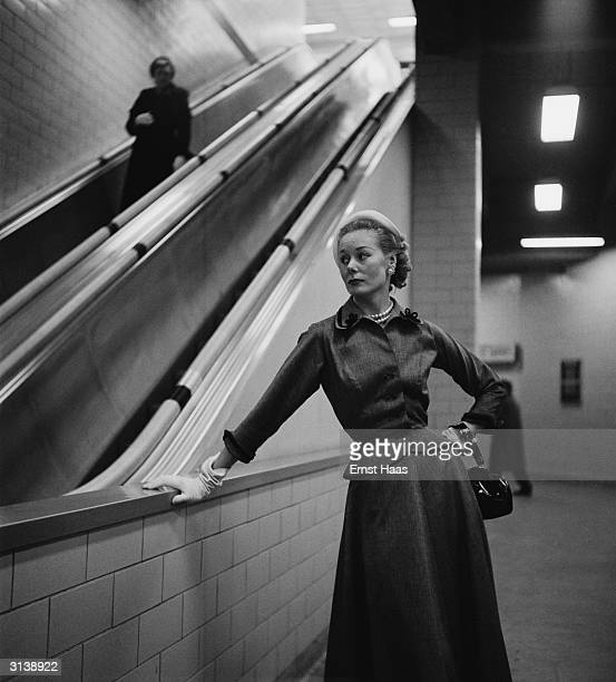 A Vogue fashion model in the New York subway wearing a skirt and a high buttoned top with a fitted waist