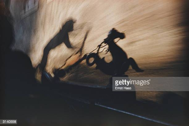 The shadow of a gondolier steering his craft along a canal in Venice at nighttime Colour Photography book