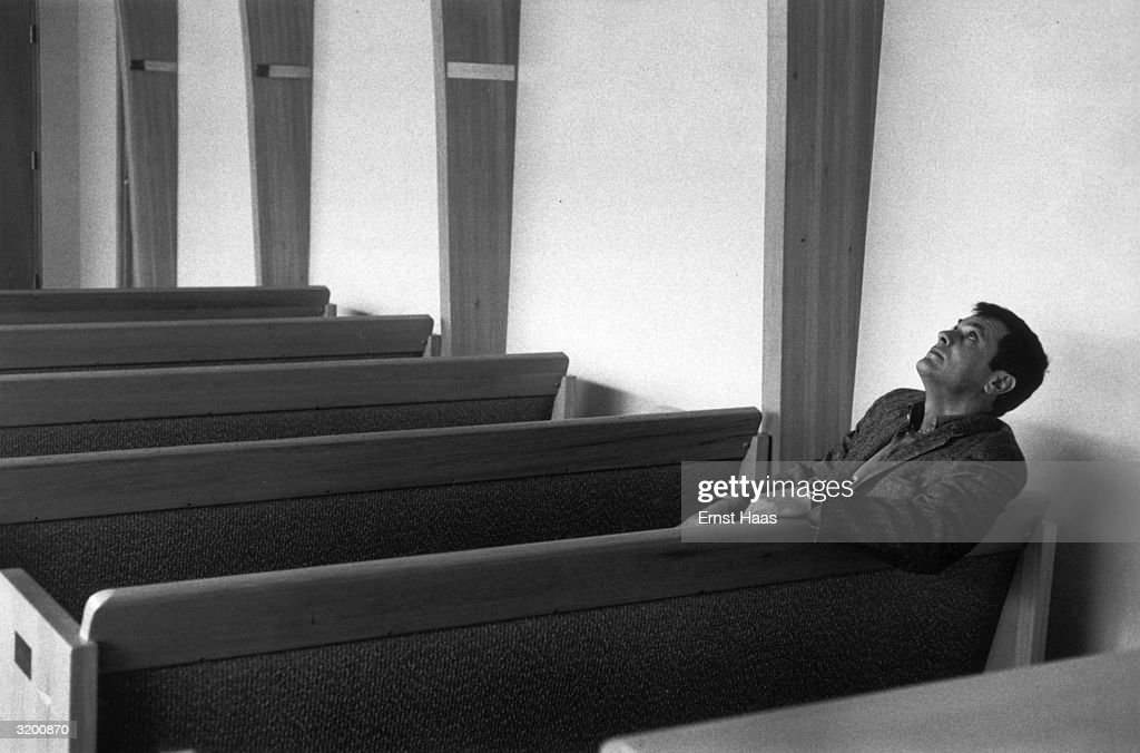 Actor Tony Curtis thoughtfully staring at the ceiling in a modern chapel.