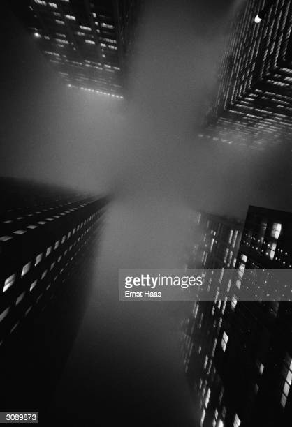 New York skyscrapers their tops hidden by nightime mist Viewed from below the mist forms a cross between the buildings In Black And White book
