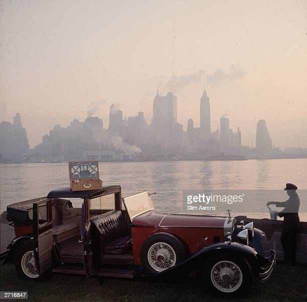 Premium Rates Apply A chauffeur unpacks a picnic hamper from a Rolls Royce against the New York skyline