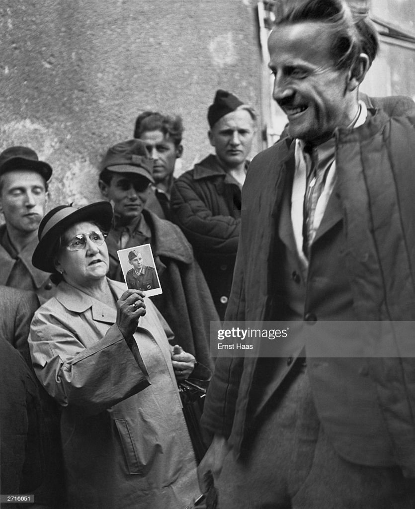 Premium Rates Apply. A smiling prisoner of war returning home to Vienna passes a woman holding a photograph up in a mixture of hope and despair. Original Publication: In black and white book