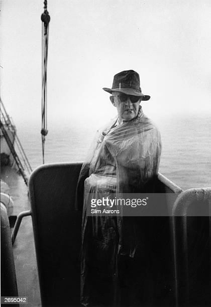 Premium Rates Apply American director John Ford wrapped up warm on the deck of the USS Reluctant during the filming of 'Mister Roberts' on location...
