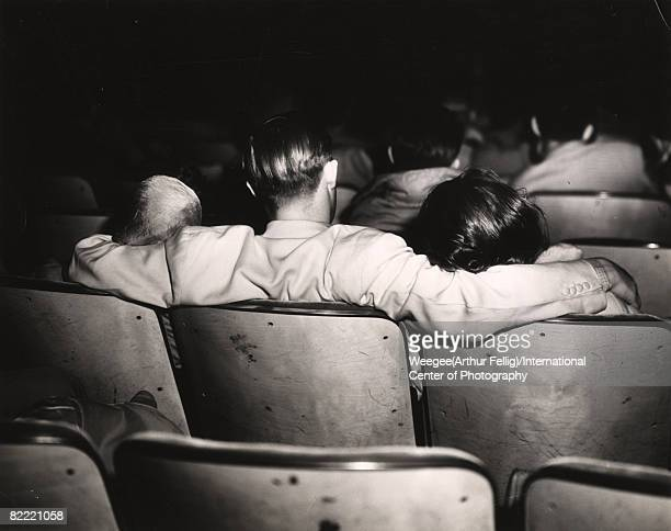 Premium Rates Apply. Back view of a man with his arms around the shoulders his companions in a movie theater, 1940s.