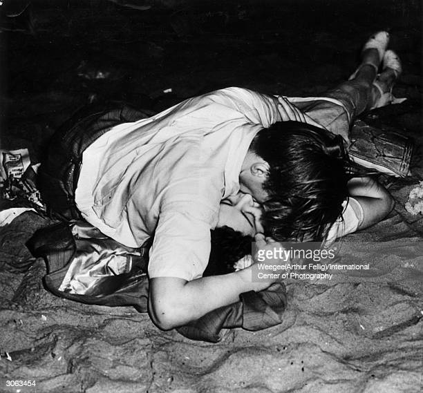 Premium Rates Apply. Circa 1943: Two lovers kissing on New York's Coney Island beach at night-time. Using infrared negative.