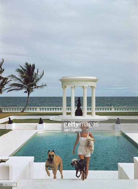 Mrs F C Winston Guest with her dogs in front of the Grecian temple pool on her oceanfront estate Villa Artemis Palm Beach Florida