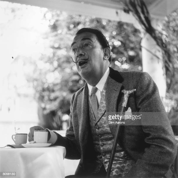 Premium Rates Apply. Circa 1955: Spanish artist Salvador Dali enjoys a cup of coffee on a terrace at the Ritz Hotel, Madrid.