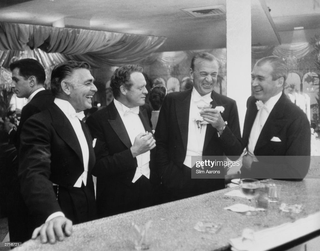 Premium Rates Apply. Film stars (left to right) Clark Gable (1901 - 1960), Van Heflin (1910 - 1971), Gary Cooper (1901 - 1961) and James Stewart (1908 - 1997) enjoy a joke at a New Year's party held at Romanoff's in Beverly Hills. Original Publication: A Wonderful Time - Slim Aarons