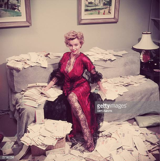 Premium Rates Apply Marilyn Monroe wearing a red negligee trimmed with black lace sorts out her fan mail shortly after her film 'The Asphalt Jungle'...