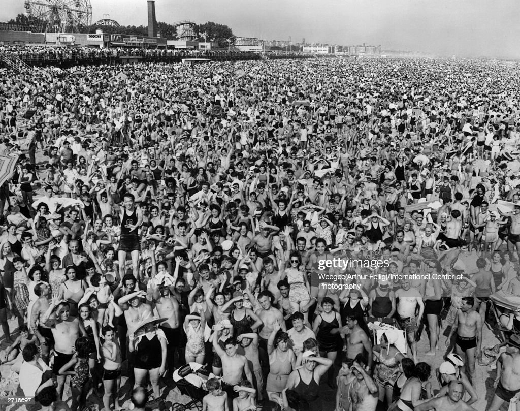 Premium Rates Apply. **NOT TO BE USED FOR POSTCARDS** A crowd of holidaymakers cover the sands of Coney Island beach, New York at four in the afternoon. (Photo by Weegee (Arthur Fellig)/International Center of Photography/Getty Images)