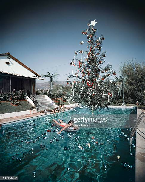 Premium Rates Apply Rita Aarons wife of photographer Slim Aarons swimming in a pool festooned with floating baubles and a decorated Christmas tree...
