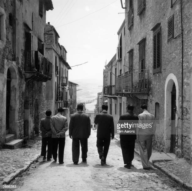 Premium Rates Apply Sicilianborn American gangster Charles 'Lucky' Luciano walking with friends in Lercara Sicily His criminal empire included...