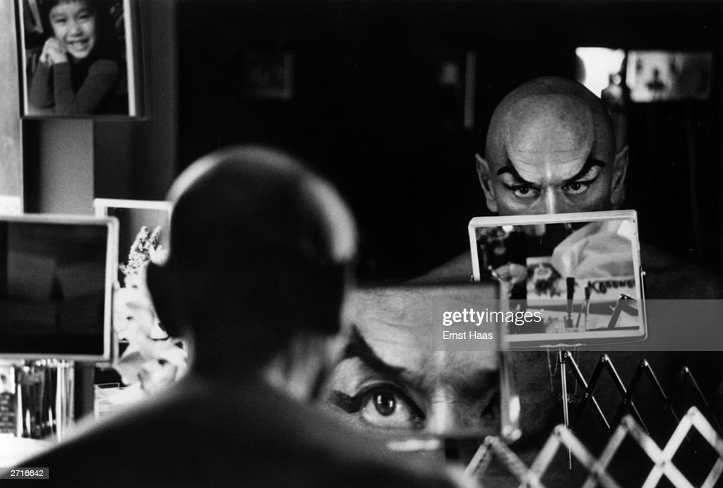 Premium Rates Apply. Yul Brynner (Taidje Khan) (1915 - 1985, does a double check on his make-up with a magnifying mirror. Original Publication: In black and white book
