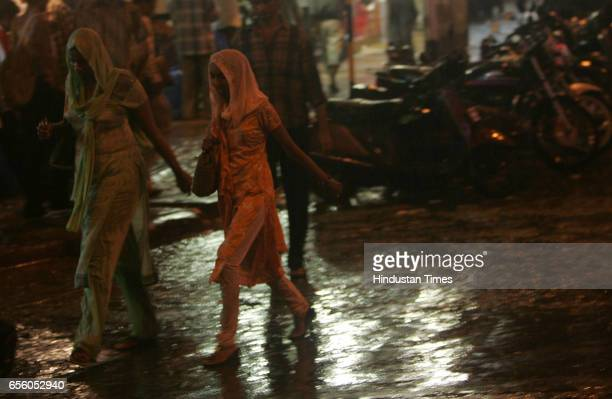 Premonsoon rain showers Girls using dupattas to shield enjoys being getting wet in the first shower city experienced