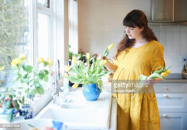 Prenant woman putting spring flowers in vase at home.