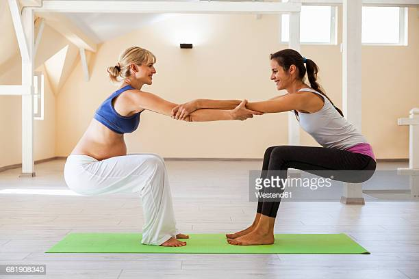 prenatal yoga, female yoga instructor, stretching - teacher bending over stock photos and pictures