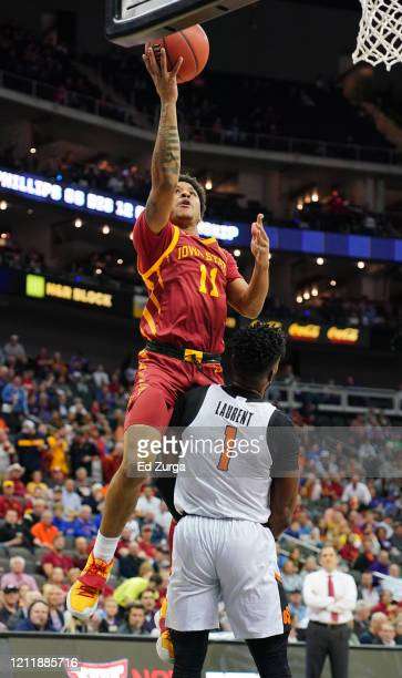 Prentiss Nixon of the Iowa State Cyclones lays the ball up and over Jonathan Laurent of the Oklahoma State Cowboys in the first half during the first...