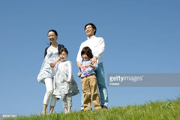 Prents with two children standing on grass