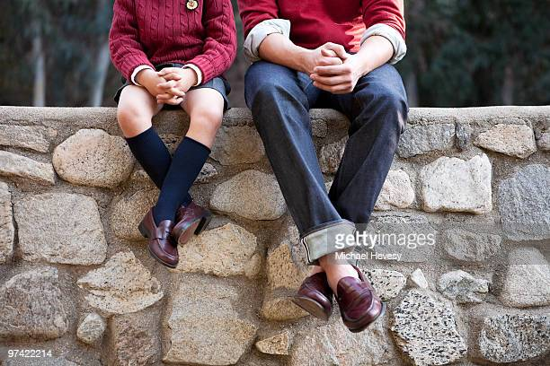 prep school students sitting on stone wall  - loafer stock pictures, royalty-free photos & images