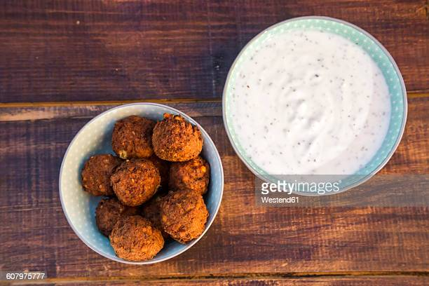 Preparation of falafel, vegetan falafel patties, joghurt in bowl