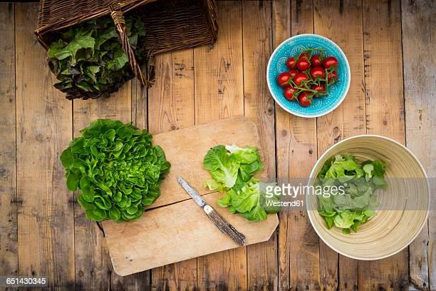 Preparation of salad, tomatoes, salanova on chopping board, knife