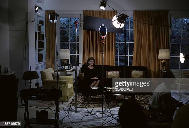 Preparation Of The Exhibition On John Fitzgerald Kennedy. Dans un salon, Jackie KENNEDY, en robe noire, assise dans un canapé, devant un fenêtre avec des rideaux, au premier plan des flashs de studio allumés.