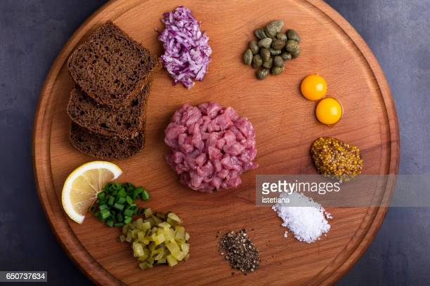 preparation steak tartare, ingredients - sliced pickles stock photos and pictures