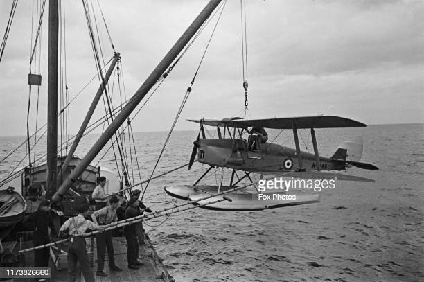 Preparations being made for the seaborne retrieval of a Fleet Air Arm De Havilland DH82B Queen Bee seaplane drone which is flown by wireless control...