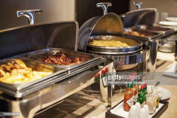 prepared food in warming dishes on buffet - buffet stock pictures, royalty-free photos & images