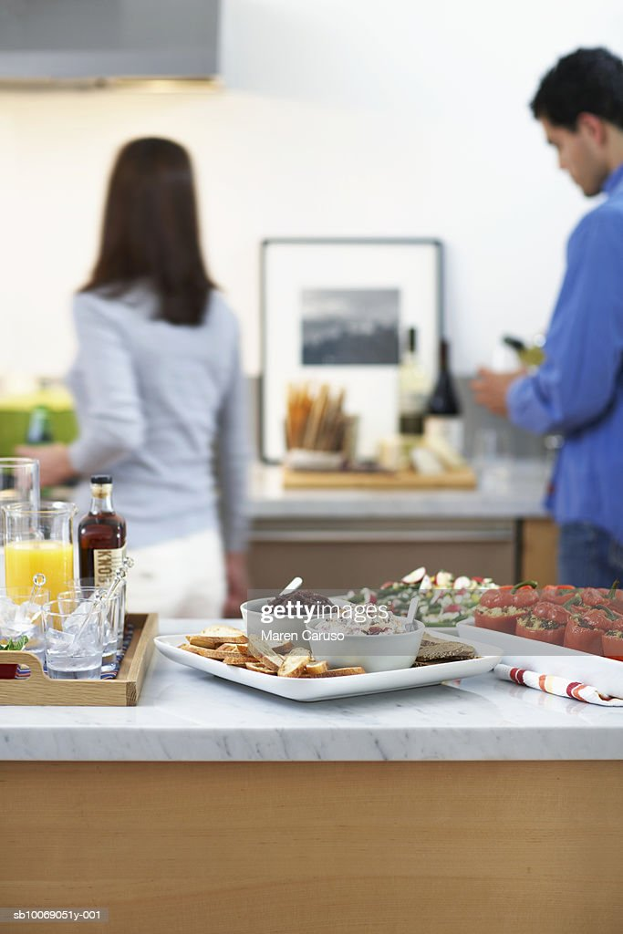 Prepared food on kitchen counter, Man and woman in background. : Stockfoto