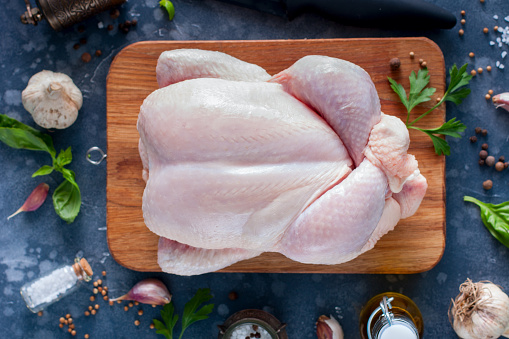 Prepared fresh raw chicken for cooking on a cutting wooden board, top view, selective focus 1042438108