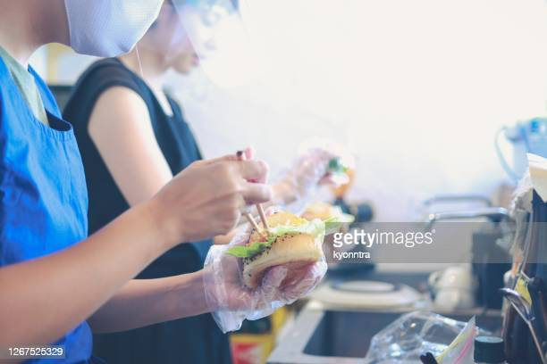 preparing a delicious fresh blt sandwich wearing mask and face shield - yōshoku imagens e fotografias de stock