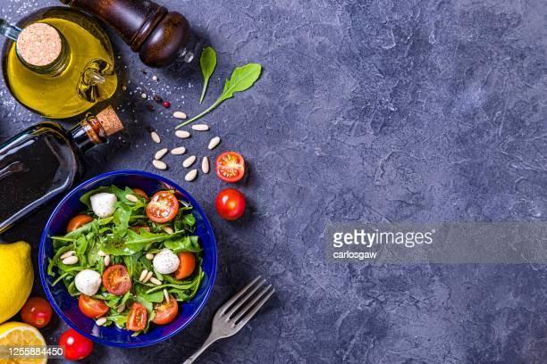 het bereiden en kruiden van een verse salade - table top shot stockfoto's en -beelden