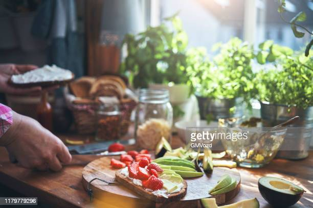 preparing avocado sandwich with brown bread, cream cheese and strawberries - cream cheese stock pictures, royalty-free photos & images