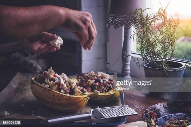 Vorbereitung gebackene Kürbisse mit Quinoa, Tomaten, Zucchini und Feta-Käse
