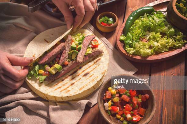 preparing beef meat tacos - tortilla flatbread stock pictures, royalty-free photos & images