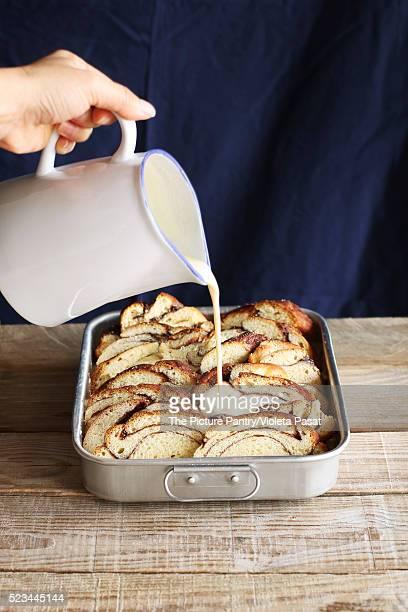 Preparing bread pudding.Pouring egg mixture over slices of brioche bread in a pan