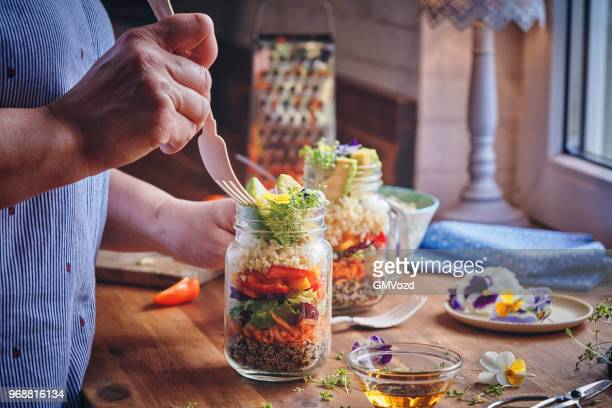 preparing bulgur salad with paprika, cucumber, onion, carrots, lettuce and quinoa served in a jar - jars with salad stock pictures, royalty-free photos & images