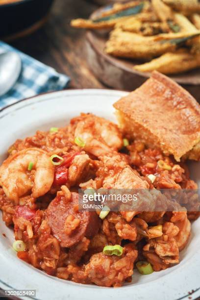 preparing cajun style chicken, shrimp and sausage jambalaya in a cast iron pot - west indian culture stock pictures, royalty-free photos & images