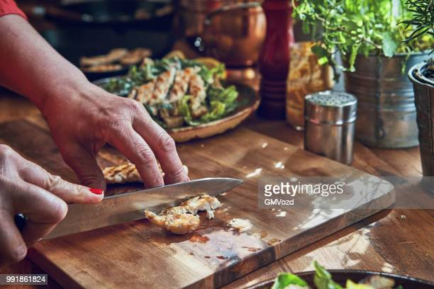 preparing cesar salad with chicken, lettuce and parmesan - crouton stock photos and pictures
