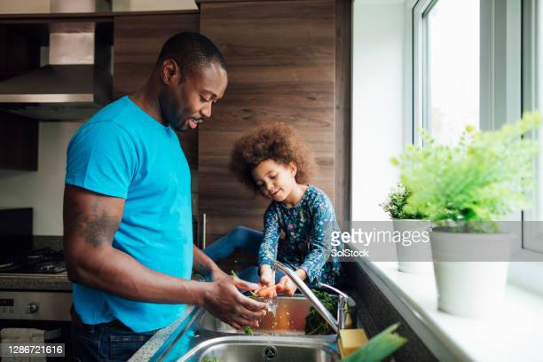 preparing dinner together - real people stock pictures, royalty-free photos & images