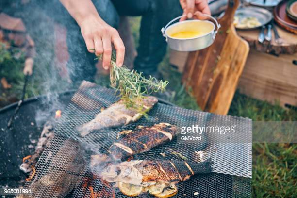 preparing fish for cooking over open campfire - warming up stock pictures, royalty-free photos & images