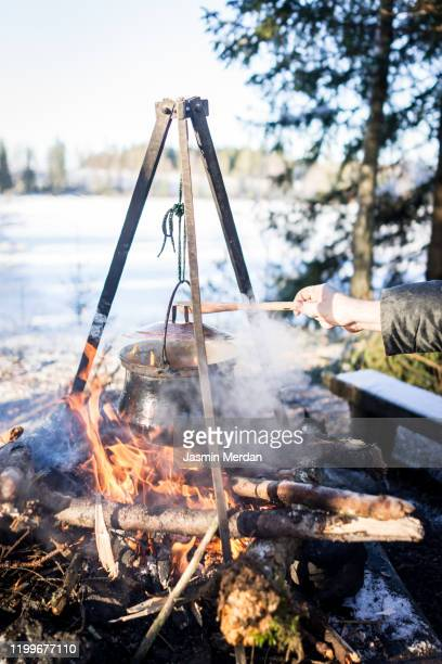 preparing food in cooking pot on campfire - simple living stock pictures, royalty-free photos & images