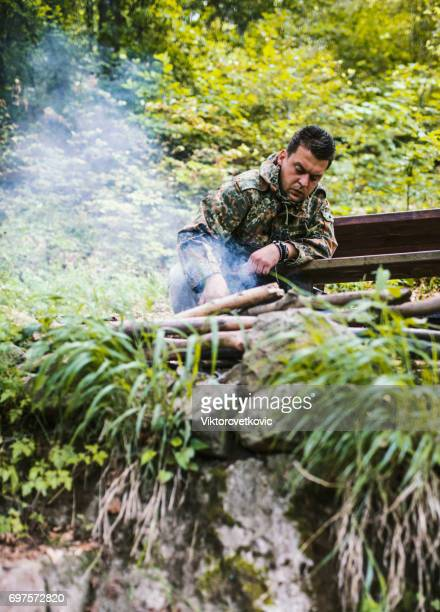 Preparing food on grill in forest